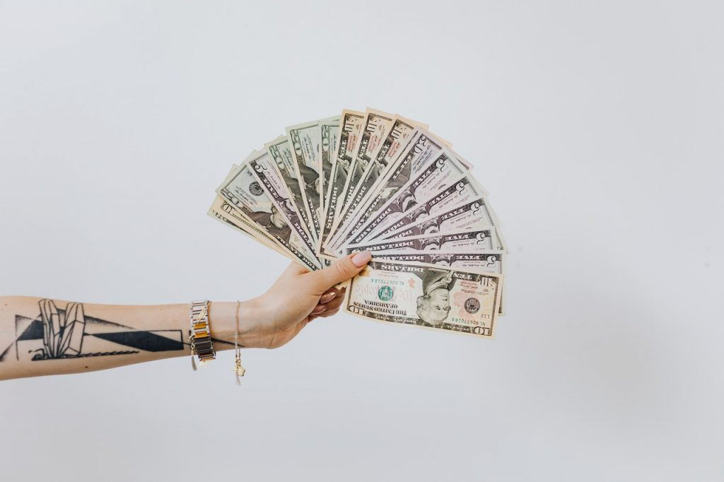 person holding money budget buy hearing aid 8 things to consider