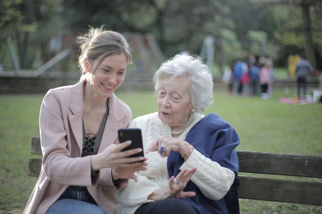 woman and older woman using phone presbycusis